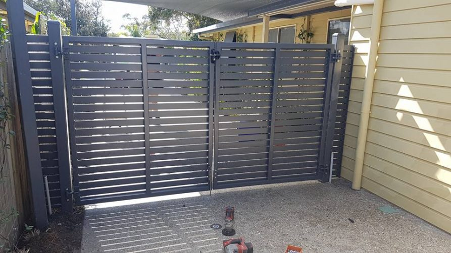 Two manual swing gates with fixed panels in the colour Iron Stone